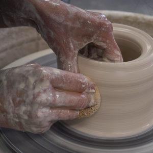 Hands throwing a pot